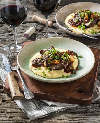 Een bord gevuld met runderstoof op een bodem van polenta