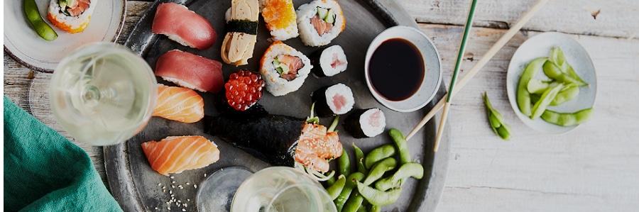 Een schaal met verschillende sushi en soja boontjes