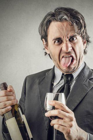Een man die vies kijkt en zijn tong uitsteekt, terwijl hij een glas wijn in z'n hand heeft