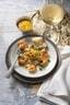 Een bord met gebakken garnalen en een sausje