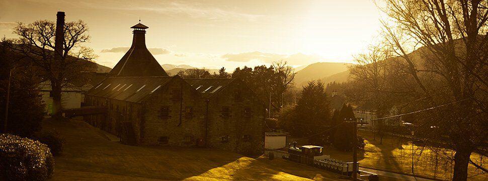 Oude distilleerderij in zonnig schots berglandschap