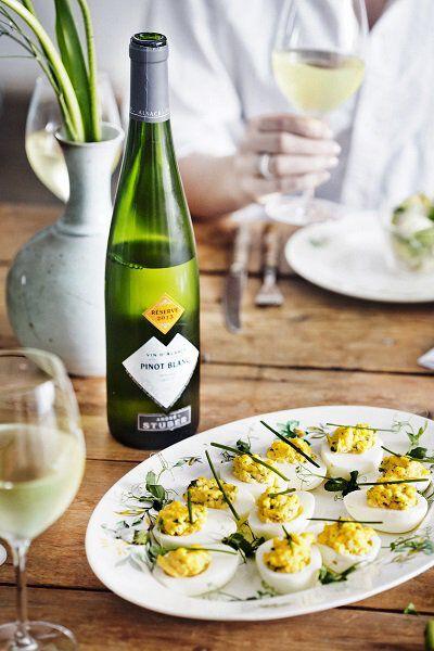 Gevulde eitjes met een fles witte wijn ernaast