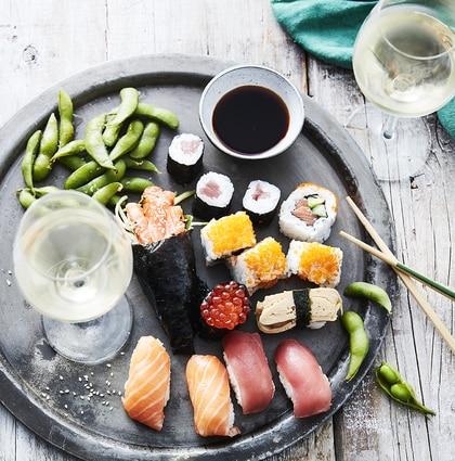 Schaal met verschillende soorten sushi en een glas witte wijn