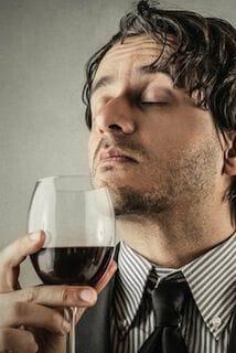 Man die ruikt aan een glas rode wijn met gesloten ogen