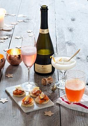 Een fles prosecco met cocktail glazen en kleine hapjes eromheen