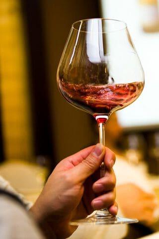 Een glas gevuld met rode wijn