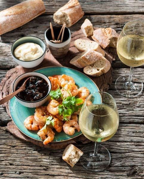 Een bord met garnalen spiesjes en wat stukjes stokbrood