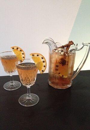 Een karaf punch met twee gevulde glazen ernaast